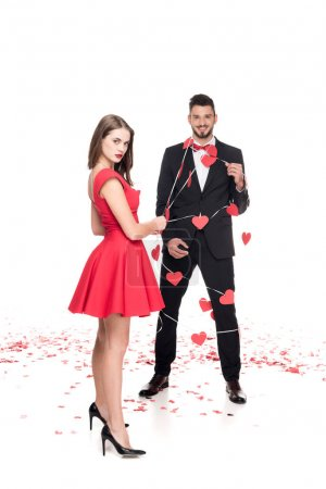 Photo for Girlfriend holding boyfriend in garland with paper hearts on white, valentines day concept - Royalty Free Image