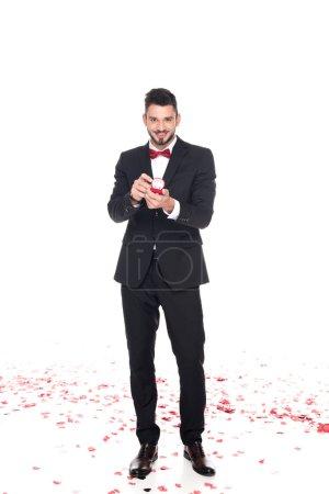 bel homme montrant une boîte rouge avec anneaux de mariage isolé sur blanc, Valentin concept