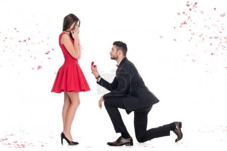 Photo pour Vue latérale du petit ami proposant petite amie et debout sur le genou isolé sur blanc, concept de Saint Valentin - image libre de droit