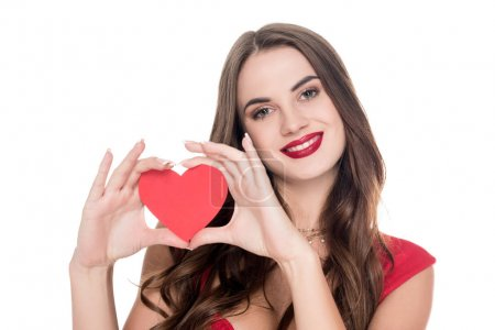smiling girl in red dress showing paper heart isolated on white, valentines day concept