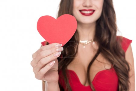 Photo for Cropped image of smiling girl in red dress showing paper heart isolated on white, valentines day concept - Royalty Free Image