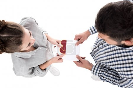 overhead view of boyfriend giving valentines postcard to girlfriend isolated on white