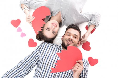 overhead view of couple lying with paper heart pieces isolated on white, valentines day concept