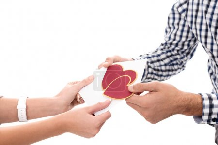 cropped image of girlfriend giving boyfriend valentines postcard isolated on white