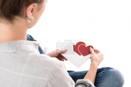 cropped image of girl holding valentines postcard and envelope isolated on white