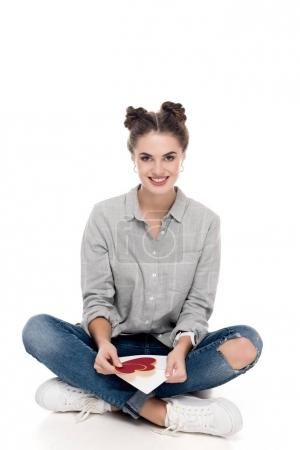 smiling girl holding valentines postcard and envelope on white