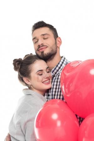 Photo pour Couple, étreindre et tenant en forme de coeur ballons isolé sur blanc, Valentin concept - image libre de droit