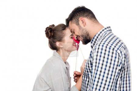 side view of attractive couple touching each other with paper hearts isolated on white, valentines day concept