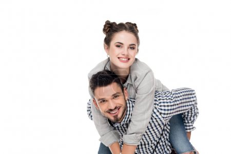 smiling boyfriend giving piggyback to girlfriend isolated on white