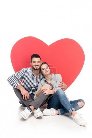 glückliches Paar sitzt neben großem Herzen auf weißem Valentinstag-Konzept