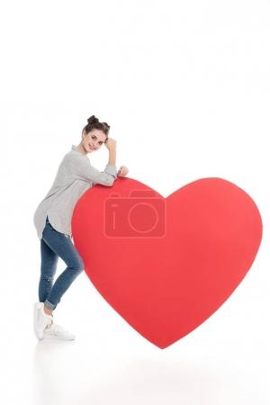 smiling girl leaning on big heart on white, valentines day concept