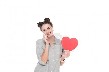 Girl holding paper heart and talking by smartphone isolated on white, valentines day