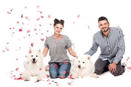 Photo pour Couple assis avec des chiens sous confettis tombant isolé sur blanc, concept de Saint Valentin - image libre de droit