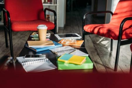 digital devices, notebooks and coffee on table at home