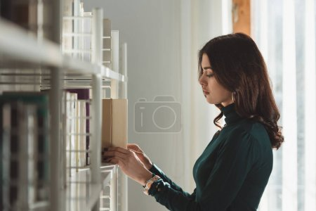 beautiful girl taking book from shelf
