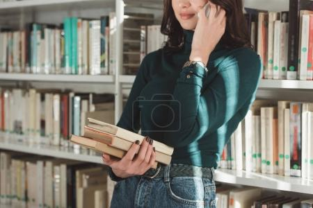 cropped image of student holding books and talking by smartphone in library