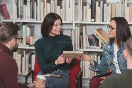 smiling multicultural friends sharing book in library