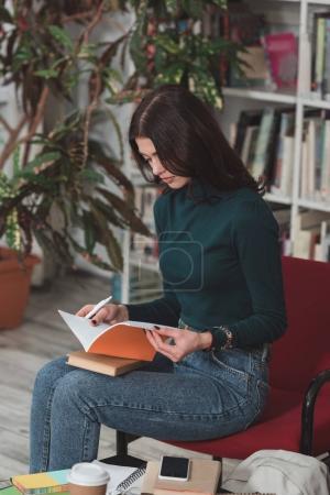 Photo pour Belle étudiante étudiant sur chaise en bibliothèque - image libre de droit