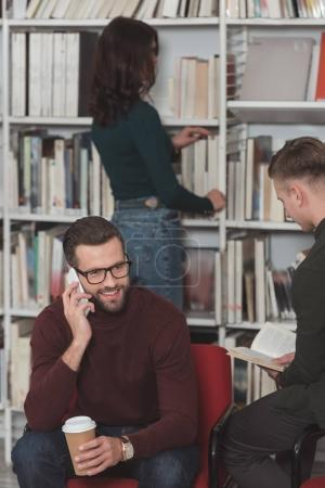 handsome student talking by smartphone in library