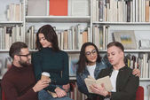 happy multicultural couples sitting on chairs in library with coffee and book
