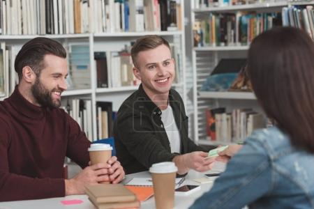 smiling students in library with disposable coffee cups
