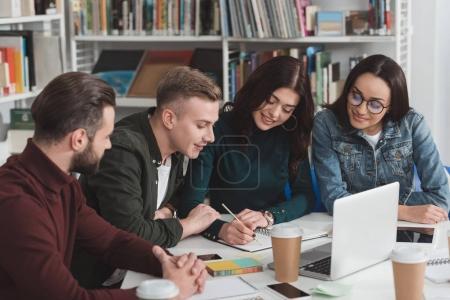 Photo pour Amis multiculturelles souriantes regardant carnet à la bibliothèque - image libre de droit
