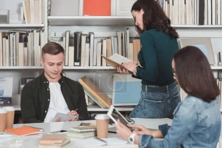 Photo for Multiethnic male and female students studying in library - Royalty Free Image