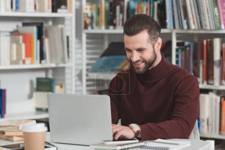 estudiante guapo sonriente con portátiles en biblioteca
