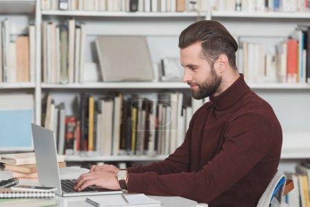 Photo pour Vue latérale du beau étudiant utilisant l'ordinateur portable dans la bibliothèque - image libre de droit