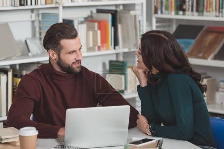 girlfriend looking at handsome boyfriend in library