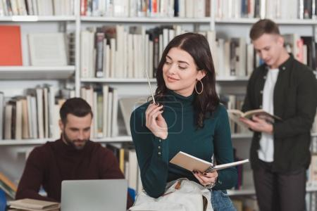 cheerful woman looking at pencil in library