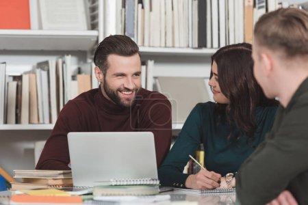 Estudiantes sonrientes sentado con el ordenador portátil en la biblioteca