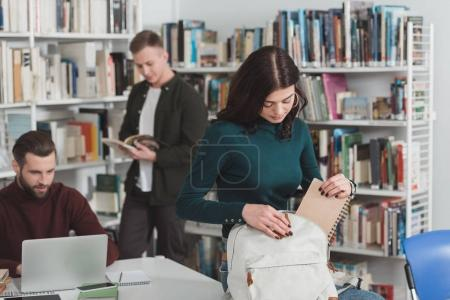 female student packing notebook in bag in library