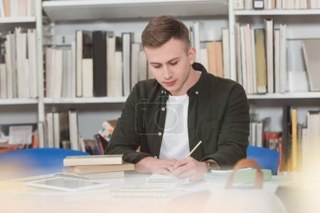 male student writing something to notebook in library
