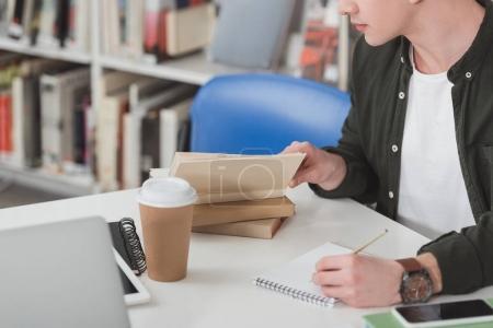 Photo pour Image recadrée de l'étudiant lire livre et prendre des notes dans la bibliothèque - image libre de droit