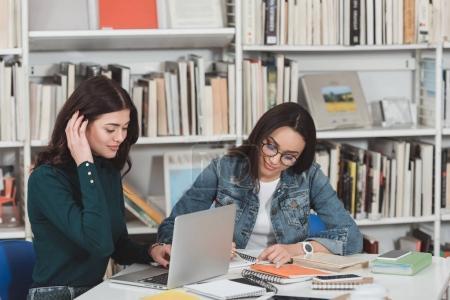 Photo pour Multicultural amies se préparent à l'examen dans la bibliothèque avec ordinateur portable et des livres - image libre de droit