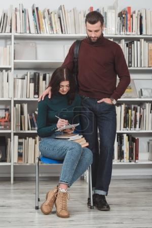 boyfriend standing near girlfriend writing something to notebook in library