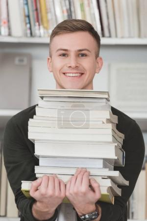 smiling student holding stack of books and looking at camera