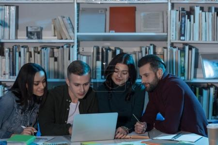 Photo pour Multiethniques amis étudiant avec ordinateur portable en bibliothèque - image libre de droit