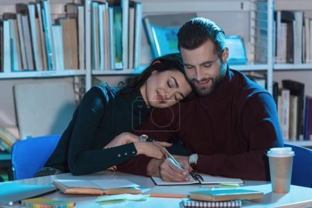 girlfriend leaning on boyfriends shoulder in library