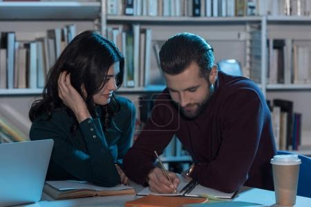 Photo for Male an female students preparing to exam in library at late evening - Royalty Free Image