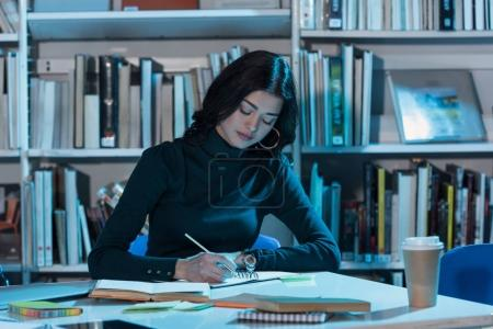 student studying in library at late evening