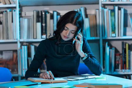 student studying in library and talking by smartphone