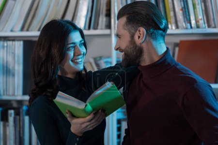 smiling couple holding book and looking at each other in library