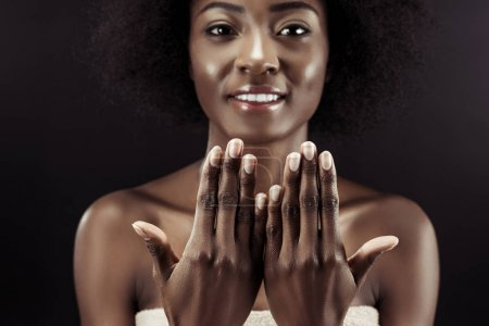 beautiful african american woman showing her nails isolated on black