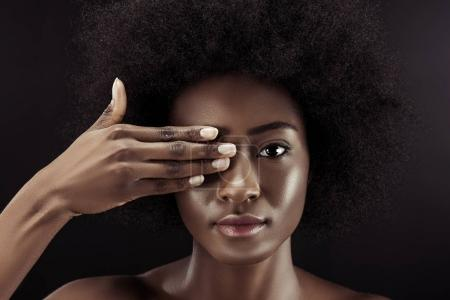 attractive african american woman covering eye with hand isolated on black