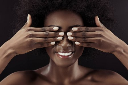Photo for Beautiful african american woman covering eyes with hands isolated on black - Royalty Free Image