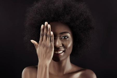 smiling african american woman covering eye with hand isolated on black