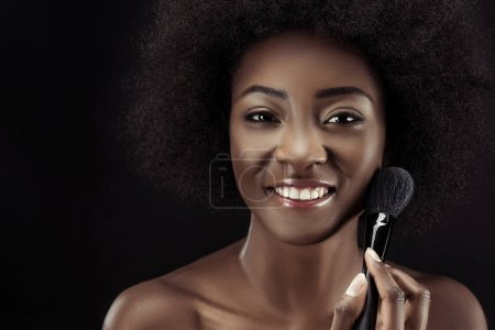 happy african american woman doing makeup with brush isolated on black