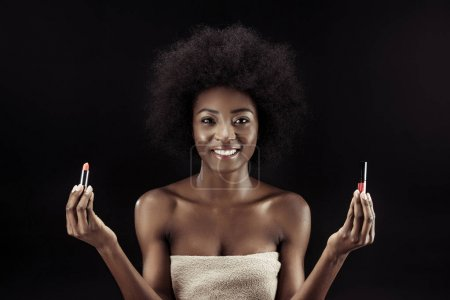 beautiful african american woman holding lipsticks isolated on black